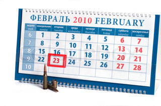 Calendar with date on February, 23rd, day of the defender of fatherland to Russia, and cartridges on a white background.