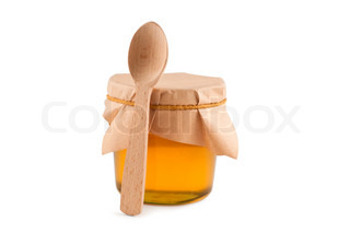 Honey in jar, spoon, isolated white.