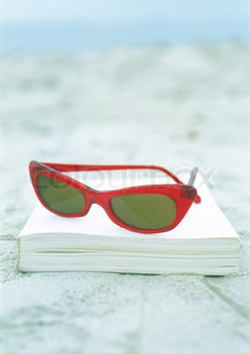 ©Michèle Constantini/AltoPress/Maxppp ; Sunglasses and book on sand