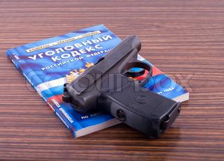 Straffeloven i Den Russiske Føderation og pistol på et skrivebord .