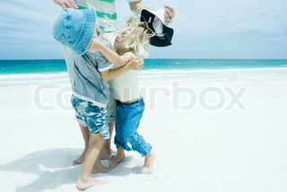 ©Sigrid Olsson/AltoPress/Maxppp ; Family on beach, boy and girl reaching for each other in front of father