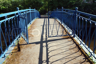 Opened gate on the narrow bridge over small river