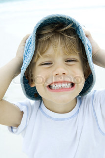 ©Sigrid Olsson/AltoPress/Maxppp ; Boy holding hat and smiling on beach, portrait