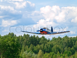 airplane landing against the cloudy sky and forest