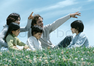 ©Laurence Mouton/AltoPress/Maxppp ; Boys and girl sitting on grass with parents pointing