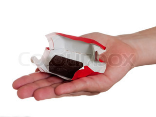 Human hand holding one sweet chocolate candy food