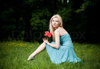 Pretty Woman With Roses Sitting On The Meadow