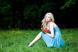 Blonde Pretty Woman Sitting On The Grass