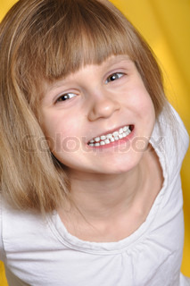 portrait of a little happy girl against the yellow background