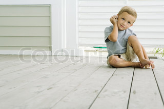 ©Laurence Mouton/AltoPress/Maxppp ; Boy sitting on the ground listening to seashell, smiling