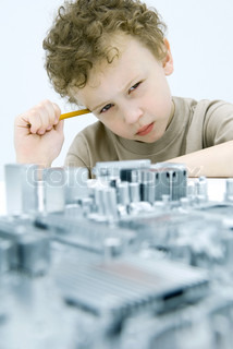 ©Odilon Dimier/AltoPress/Maxppp ; Little boy with circuit board, holding pencil, looking at camera
