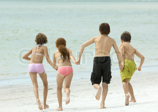 ©Odilon Dimier/AltoPress/Maxppp ; Four kids holding hands and running toward water, on beach, rear view