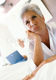 ©Téo Lannié/AltoPress/Maxppp ; Senior woman with hand under chin, frowning, man using laptop in background