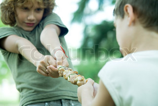 ©Ale Ventura/AltoPress/Maxppp ; Two boys playing tug-of-war with grilled kebab