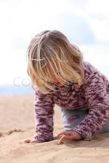 A little girl writing in the sand. Soft focus front and back