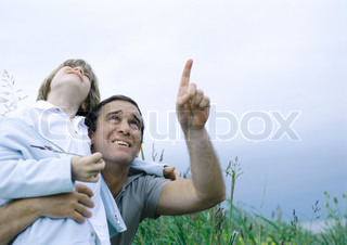 ©Laurence Mouton/AltoPress/Maxppp ; Man holding son in arms pointing to overcast sky