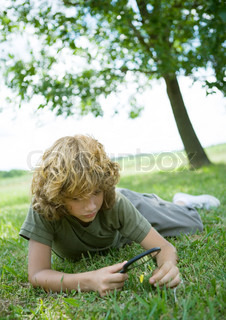©Sigrid Olsson/AltoPress/Maxppp ; Boy lying in grass, looking through magnifying glass at flower
