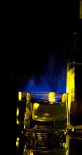 Dark blue flame of burning alcoholic drinks on a black background.
