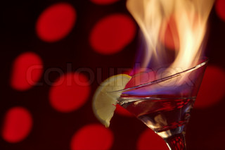 Blue flame of burning alcoholic drinks on a red background.