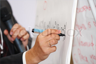 Hand with a marker writing under a white board