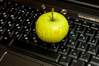 Computer keyboard and green apple close up