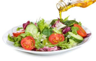 vegetabilsk salat med olivenolie hælde fra en flaske på hvid baggrund