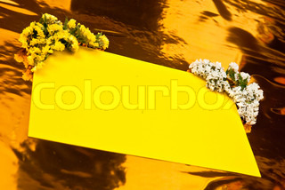 Yellow paper with flowers on yellow background