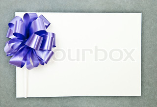 White paper blank with bow on grey background
