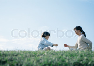 ©Laurence Mouton/AltoPress/Maxppp ; Boy and girl sitting on grass playing rock paper scissors
