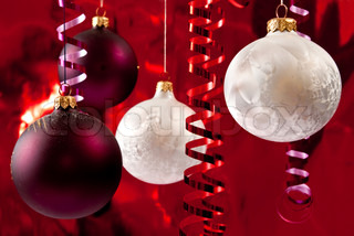 Christmas baubles and ribbons on red background
