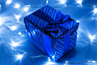 Blue gift box with garland background. Studio shot