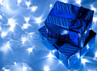 Two blue gifts boxes with garland background. Studio shot