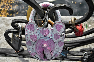 White with painted pink serrdechkami padlock close to the fence on the background of other castles, water, concrete fences