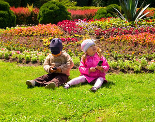 Boy and girl playing in the park with  mobile phones
