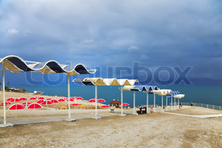 Red beach umbrellas on empty deserted deserted coast of the Dead Sea in a thunder-storm