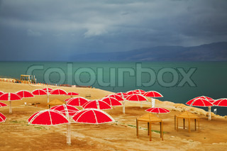 Red beach umbrellas on empty coast of the Dead Sea in thunder-storm