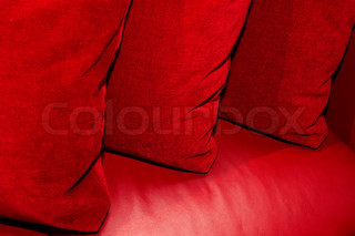 Three red pillows on a leather sofa