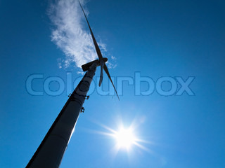 Moving wind turbine with bright blue sky