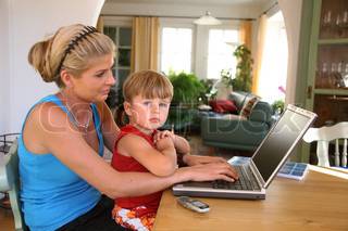 Mother with little boy look on laptop and teleworking