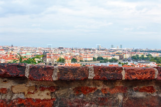 Fragment of old brick wall with old city and sky on background