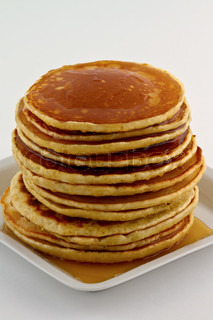 Stack of homemade pancakes with syrup on a white plate.