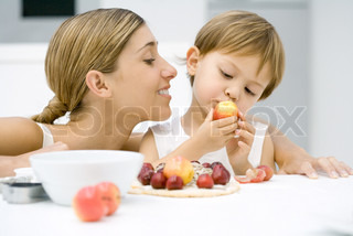 ?Laurence Mouton/AltoPress/Maxppp ; Mother and son preparing food together, boy looking at plum