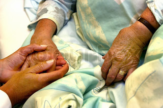 The doctor holding an elderly woman's hand.