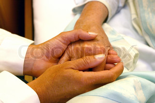 Lægen holder en ældre kvindes hånd.