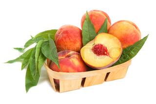 Ripe peaches heap with leaves in a basket on white background