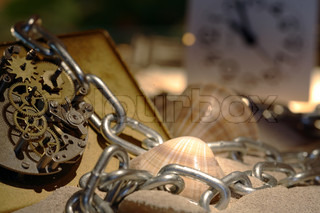 Abstract background with old clock mechanism standing on sand with stones and shells and chain