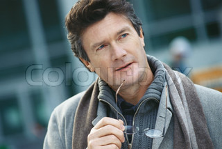 ?Eric Audras/AltoPress/Maxppp ; Mature man holding glasses to chin, looking away