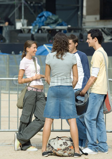 ?Laurence Mouton/AltoPress/Maxppp ; Teenagers talking in front of barrier, outdoor concert stage in background
