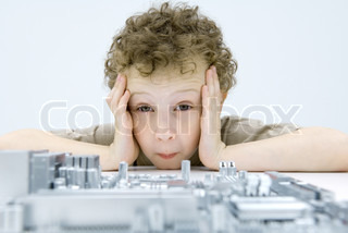 ?Odilon Dimier/AltoPress/Maxppp ; Little boy looking at circuit board, holding head, raising eyebrows