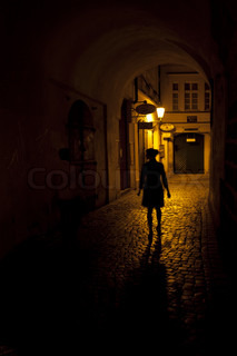 silhouette of a woman in an arch on the street